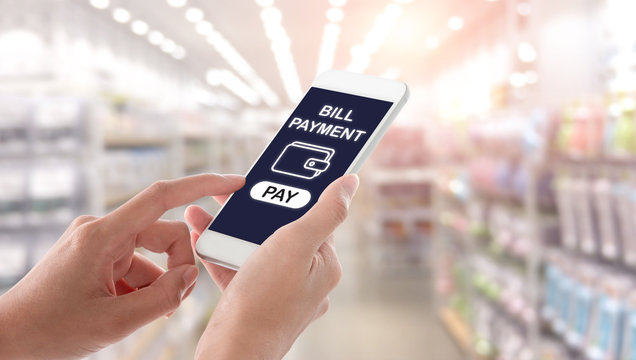 Woman hands holding and using smartphone with bill payment screen on blurred shopping mall interior background. Ecommerce concept.