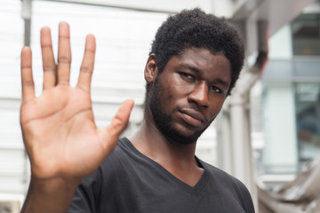 angry upset african man pointing up stop hand sign; portrait of frustrated upset african man or black man with stop or halt hand gesture; failure, rejecting, stop concept; adult african man model