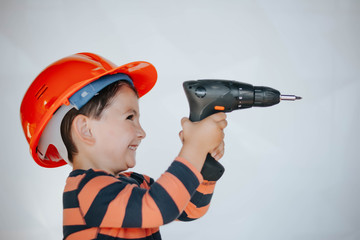 little builder in the helmet with a drill and saw the work of thinking about the future