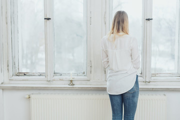 Blonde woman standing by window in bright room