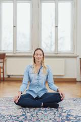 Blonde woman sitting cross-legged on floor