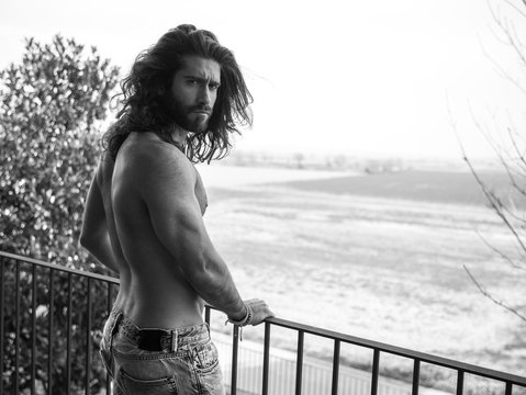 man with long hair on the terrace