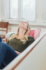 happy young woman relaxing on the couch at home