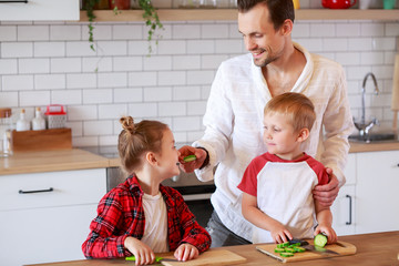 Image of young father with daughter and son cooking at table