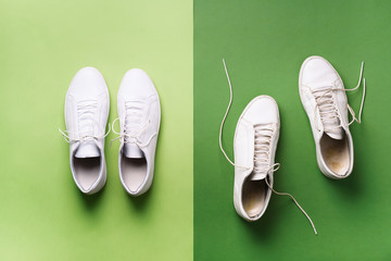 Old dirty sneakers vs new white sneakers on green background. Trendy footwear. Top view. Concept of experience, discipline and chaos, accuracy \ mess, stylish shoes. Back to school