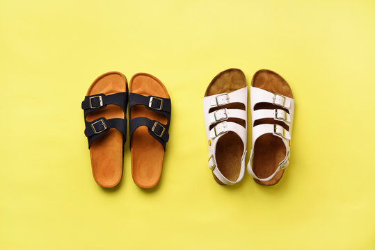 Summer female shoes - sandals (birkenstock) and slippers on yellow background with copy space. Top view. Minimal flat lay. Selection concept