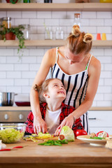 Image of young mother with her daughter cutting vegetables in kitchen