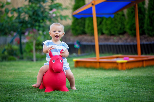 Little toddler child, boy, riding plastic horse toy in backyard