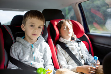 Three children, boys, siblings, traveling in car seats