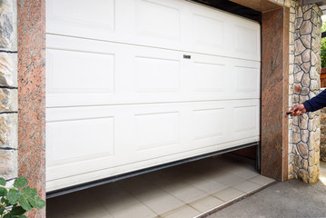 Garage door PVC. Hand use remote controller for closing and opening garage door Wall mural