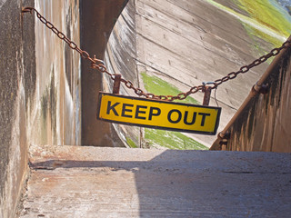 yellow keep out sign hung on a chain blocking the entrance to concrete sea wall leading to the beach at high tide