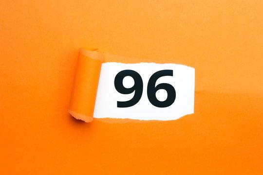 Zahl sechsundneunzig - 96 verdeckt unter aufgerissenem orangen Papier