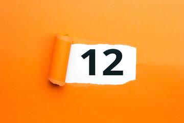 Zahl zwölf - 12 verdeckt unter aufgerissenem orangen Papier