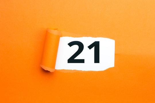 Zahl einundzwanzig - 21 verdeckt unter aufgerissenem orangen Papier