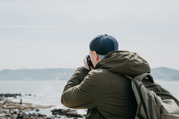 A professional photographer or a tourist man photographs a beautiful view of the sea in Lisbon in Portugal