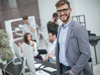 modern young businessman on the background of the workplace