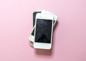 pile of old broken mobile phones with pink background