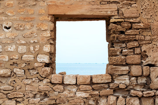 Stone wall with a square opening. Sea view. Old fortress. The Island Of Djerba. Tunisia