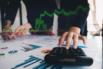Close up Businessman and partner using calculator for calaulating financial document, tax, accounting, statistics and analytic research concept