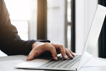 Male hands using laptop in modern office, - Business Fintech Concept