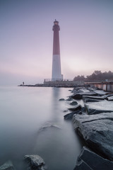 Lighthouse view with fishermen during sunrise