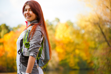 Photo of smiling woman with backpack and bicycle helmet