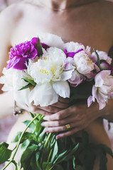 Sensual girl with bunch of colorful peony flowers in her hands