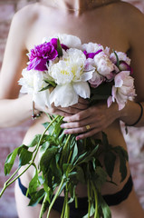 Sensual woman in black underwear with bunch of peony covering her naked body