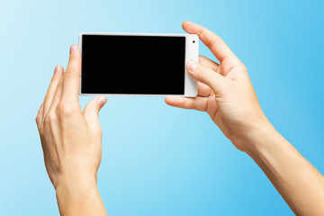 Mockup of female hands holding white frameless cellphone with black screen and making selfie at isolated blue background.
