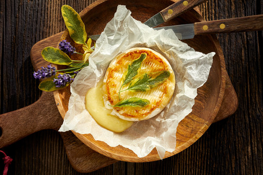 Grilled Camembert cheese with addition aromatic herbs, top view. Vegetarian food, barbecue.