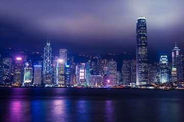 Hong Kong skyline on Victoria Harbour with moody mist and clouds in sky