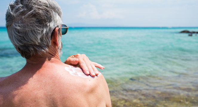Senior man applying sun lotion on summer vacation