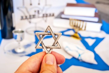 "Hand holding a David Star (""Magen David"" in Hebrew), a traditional Jewish religious symbol. With more Jewish symbols on the background: prayer books, menorah lampstand, kiddush wine blessing glass"