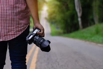 Professional photographer hand holding dslr camera.