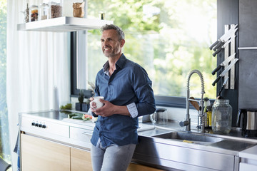Smiling mature man at home in kitchen with cup of coffee