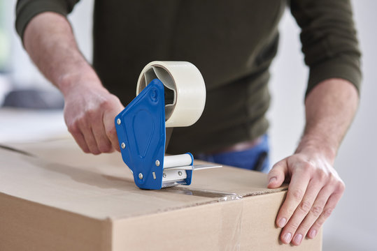 Close-up of man taping cardboard box