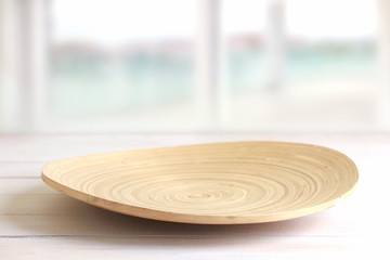 Empty wooden plate on table.