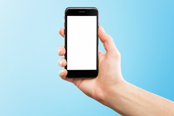 Male hand holding black cellphone isolated at blue background.