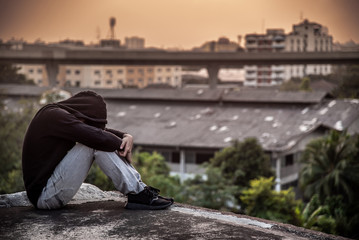 Young Asian man sitting on rooftop of abandoned building with depression stress out during sunset time in the city. Major depressive disorder concept