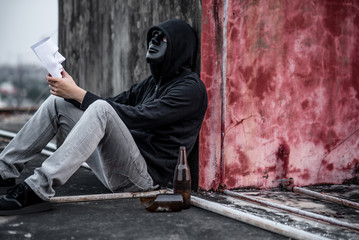 Mystery man wearing black mask and hoody jacket holding white mask sitting on rooftop of abandoned building, depression self destruction suicidal addiction massive depressive disorder concept