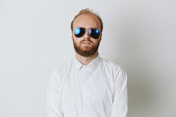 Serios fashionable young hipster bearded man wearing sunglasses and a white shirt.