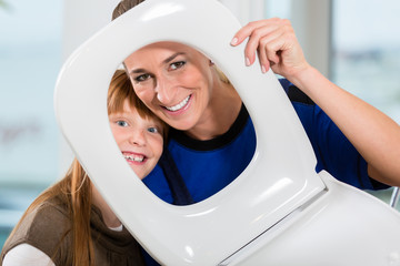 Portrait of a woman and her daughter looking at camera through a toilet seat