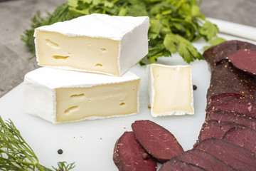 Three pieces of soft cheese with white mold and dried meat on a cutting board with greens
