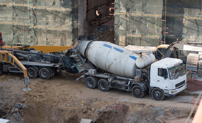 Workers at building site are pouring concrete in mold from mixer truck.