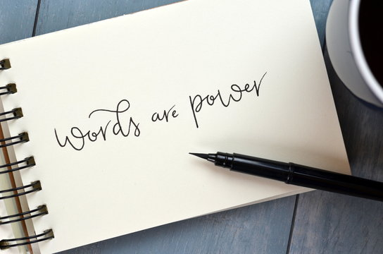 WORDS ARE POWER hand-lettered in notepad with cup of coffee on desk