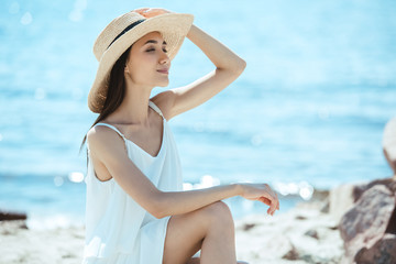 smiling asian woman in straw hat and white dress by sea