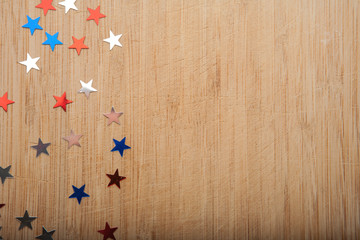 Confetti stars on wooden background. 4th July, Independence day, card, invitation in usa flag colors. View from Top , empty space.