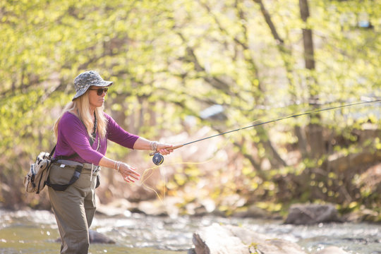 Active Woman Releasing Fly Fishing Line