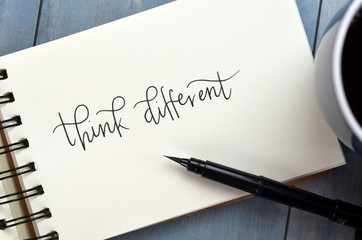 THINK DIFFERENT hand-lettered in notepad with cup of coffee on desk