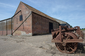 Agricultural shed building and vintage farm machinery in rural Norfolk.